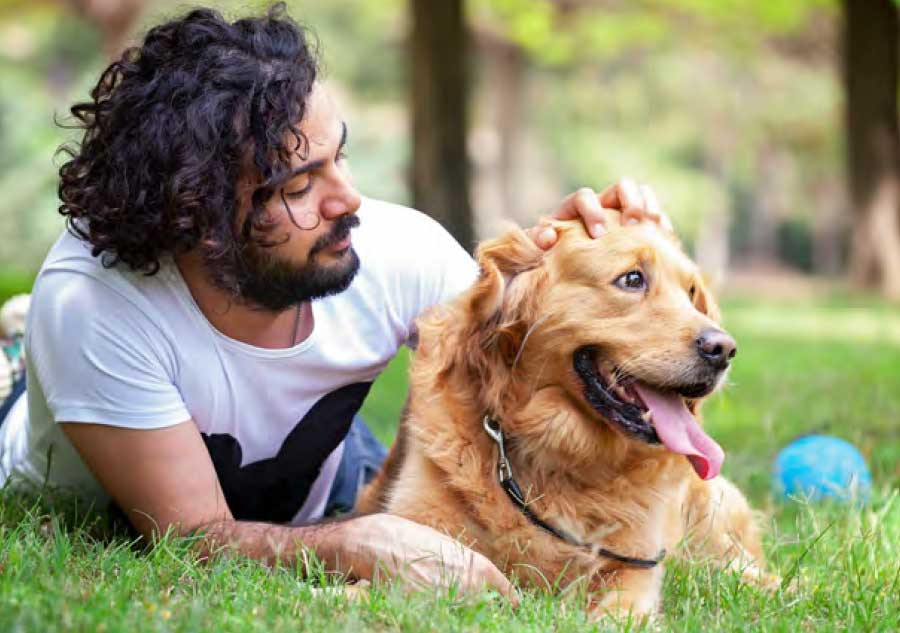 man_laying_with_dog_in_park