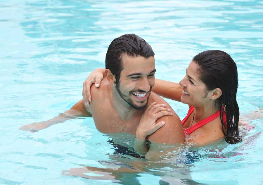 couple_swimming_in_pool_smiling
