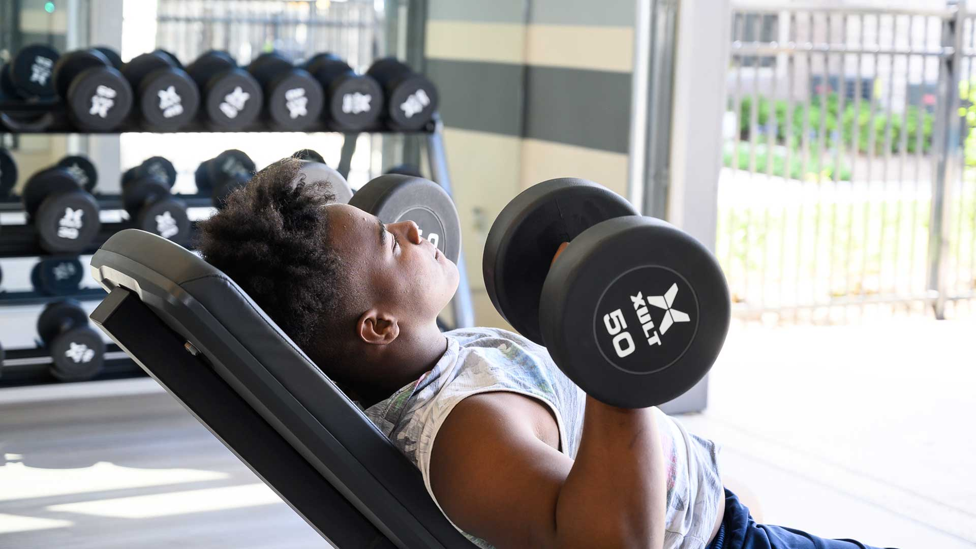 Lifting free weights in fitness center